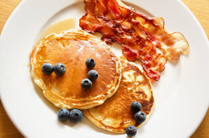 Amerikanska pannkakor med blåbär, lönnsirap och stekt bacon